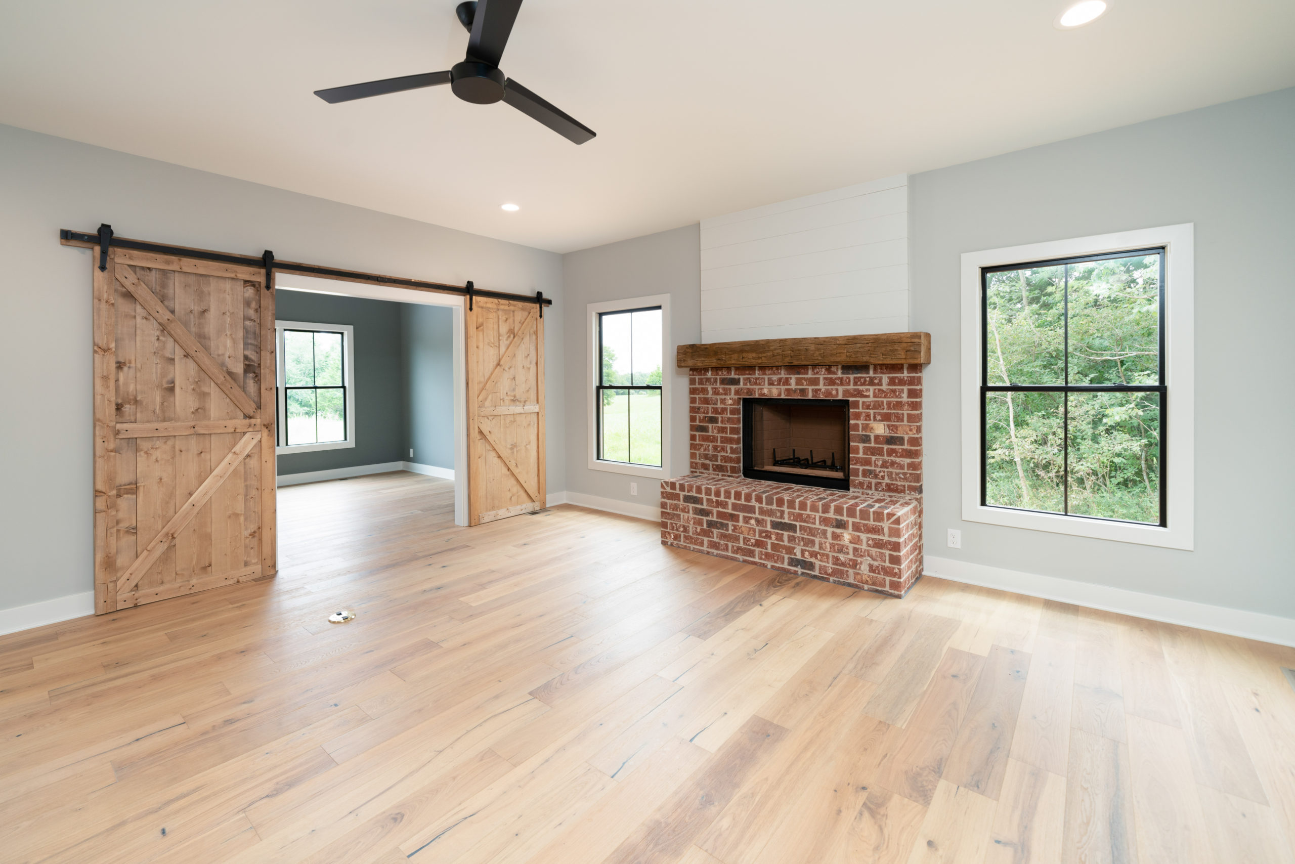 brick fireplace in living room with wood barn doors