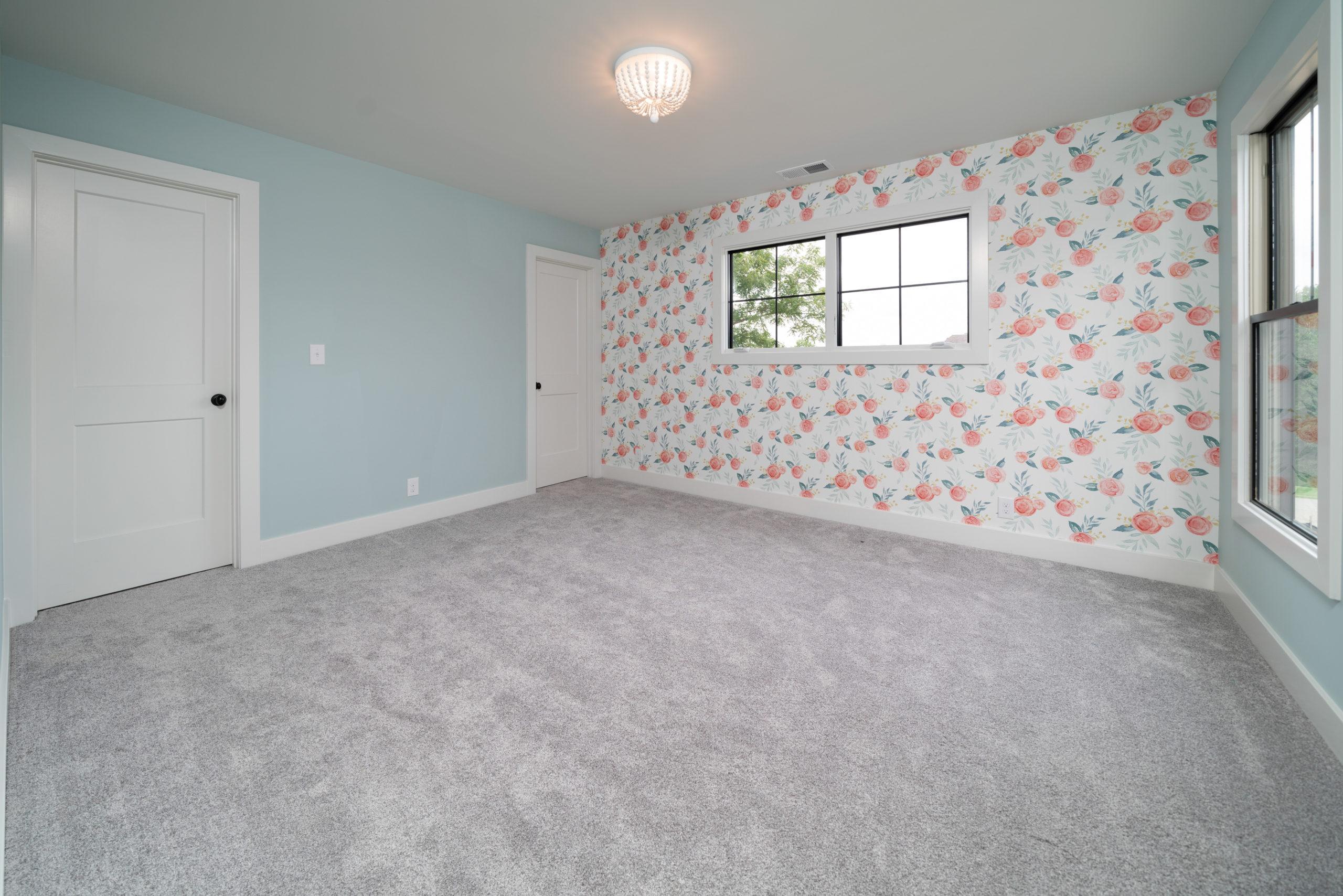 flower wallpaper accent wall in girls bedroom