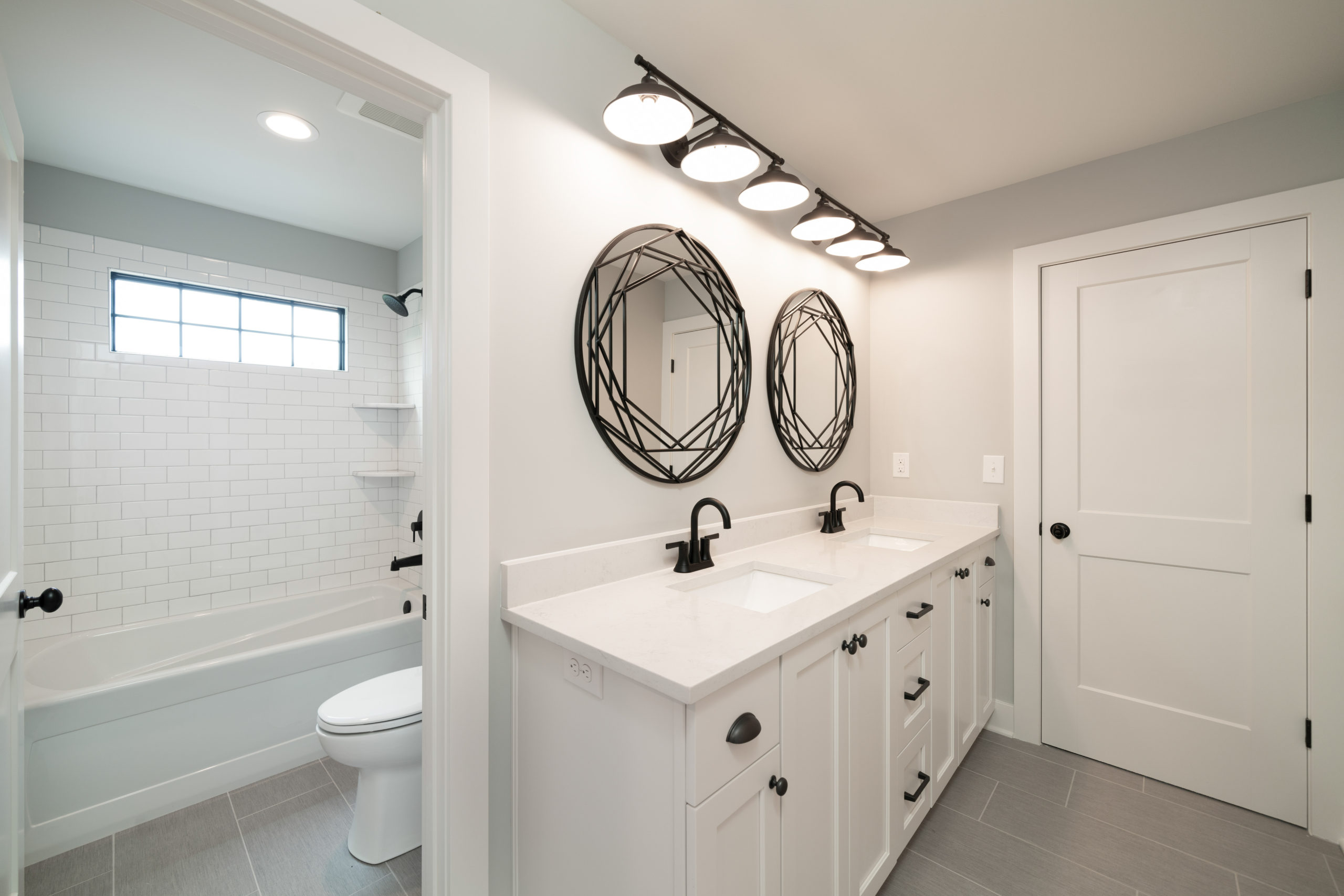 black and white bathroom design with geometric mirrors