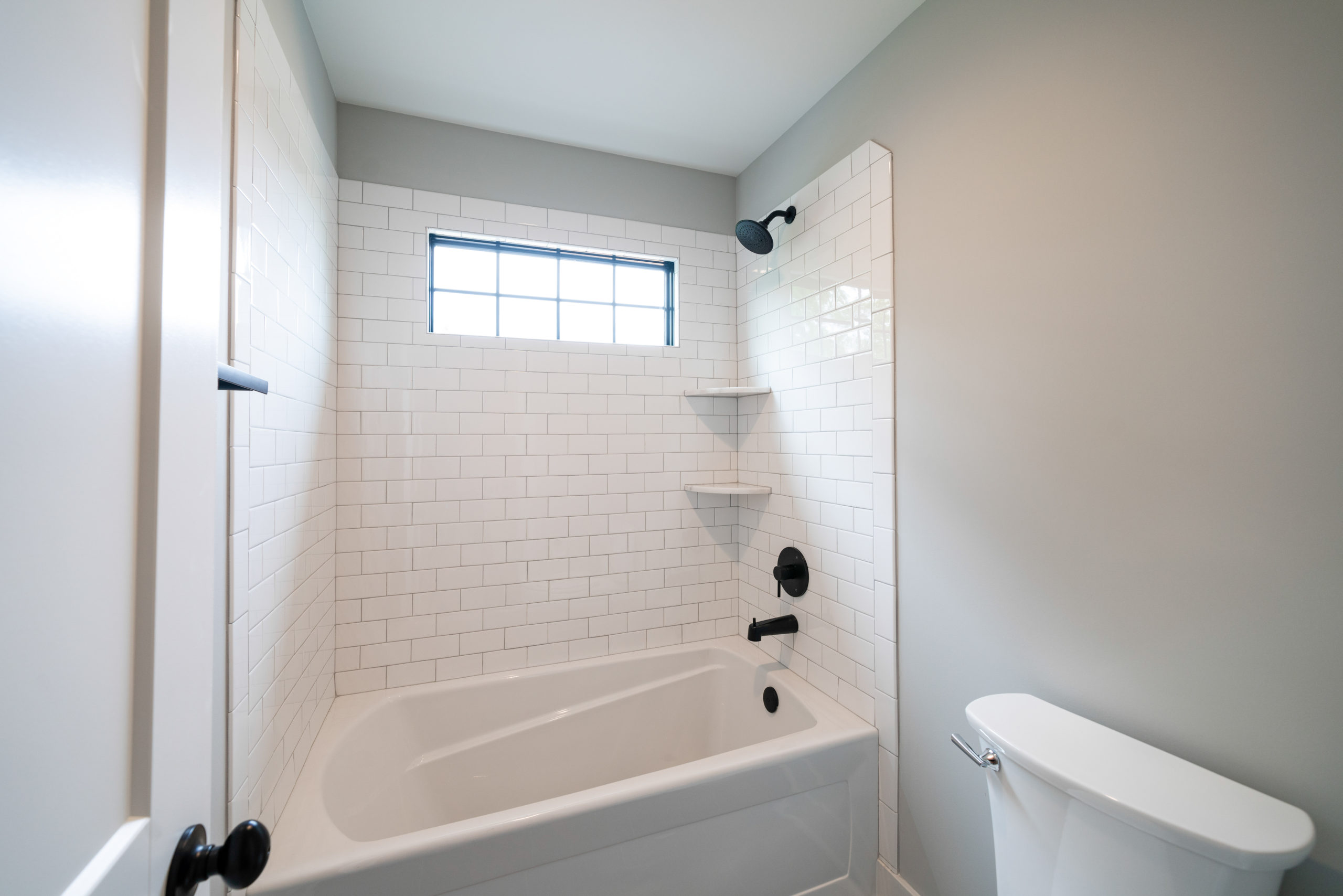 combination tub shower with white subway tile and black hardware