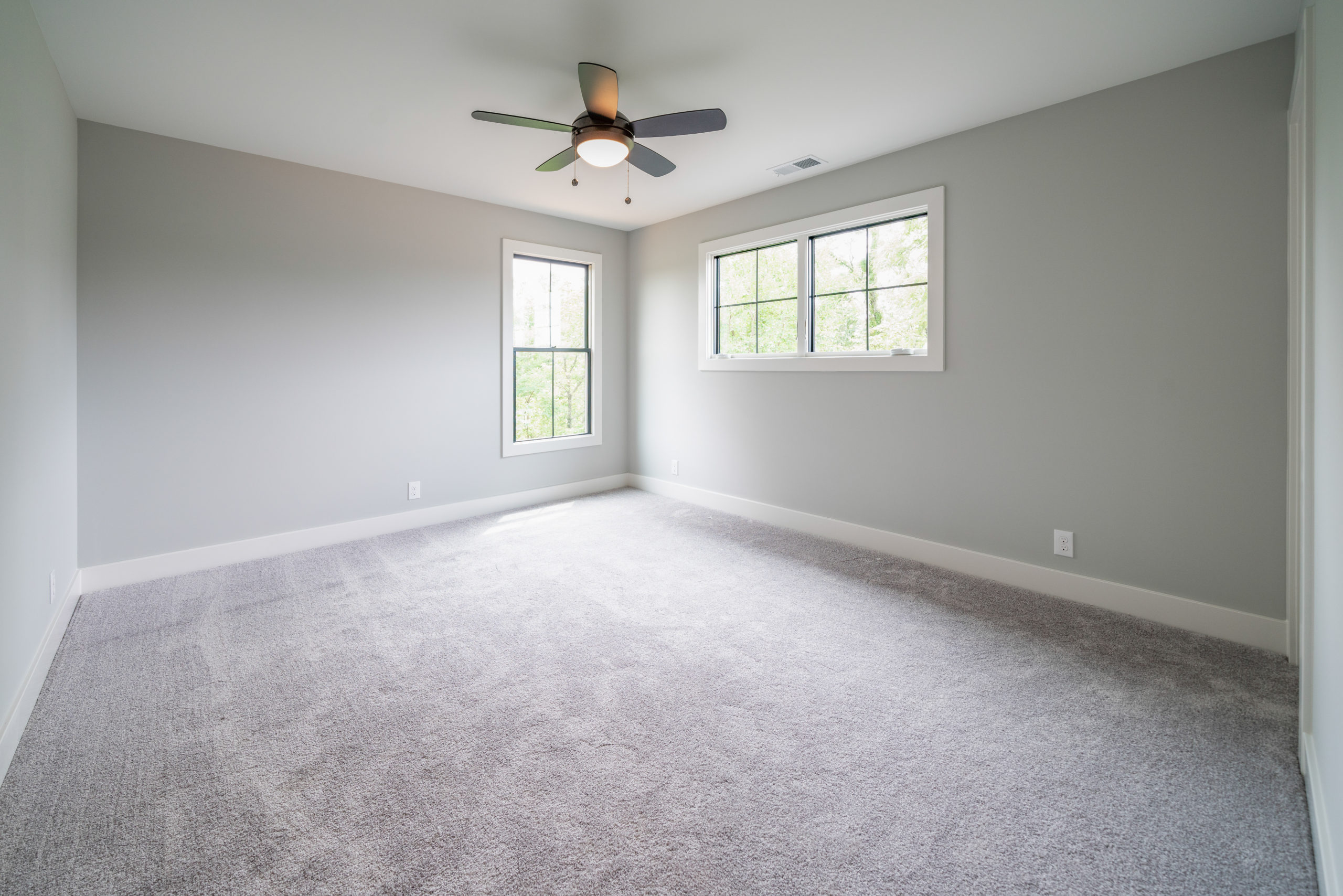 gray carpeted bedroom with ceiling fan