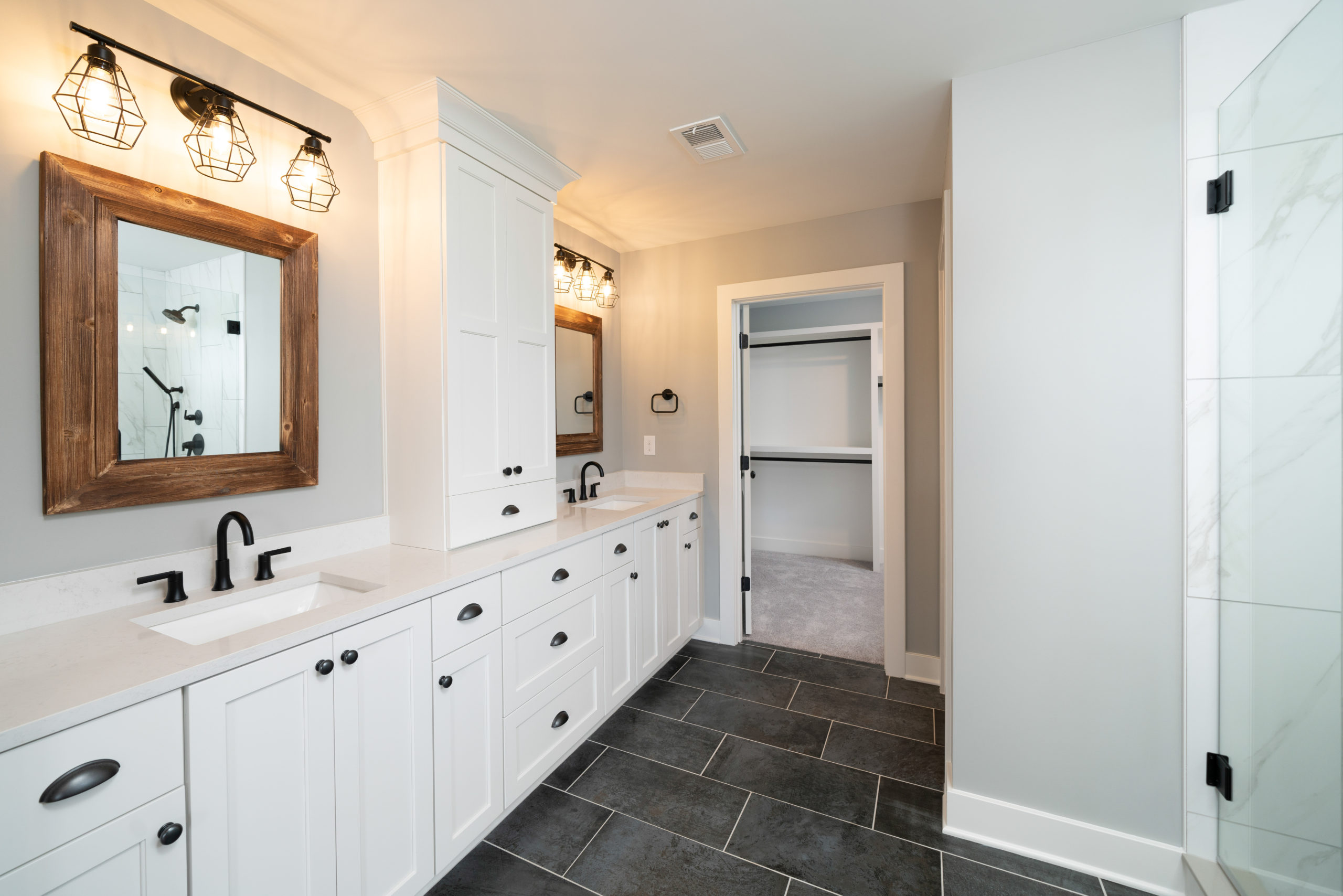 master bathroom with white vanity and wood farmhouse mirrors