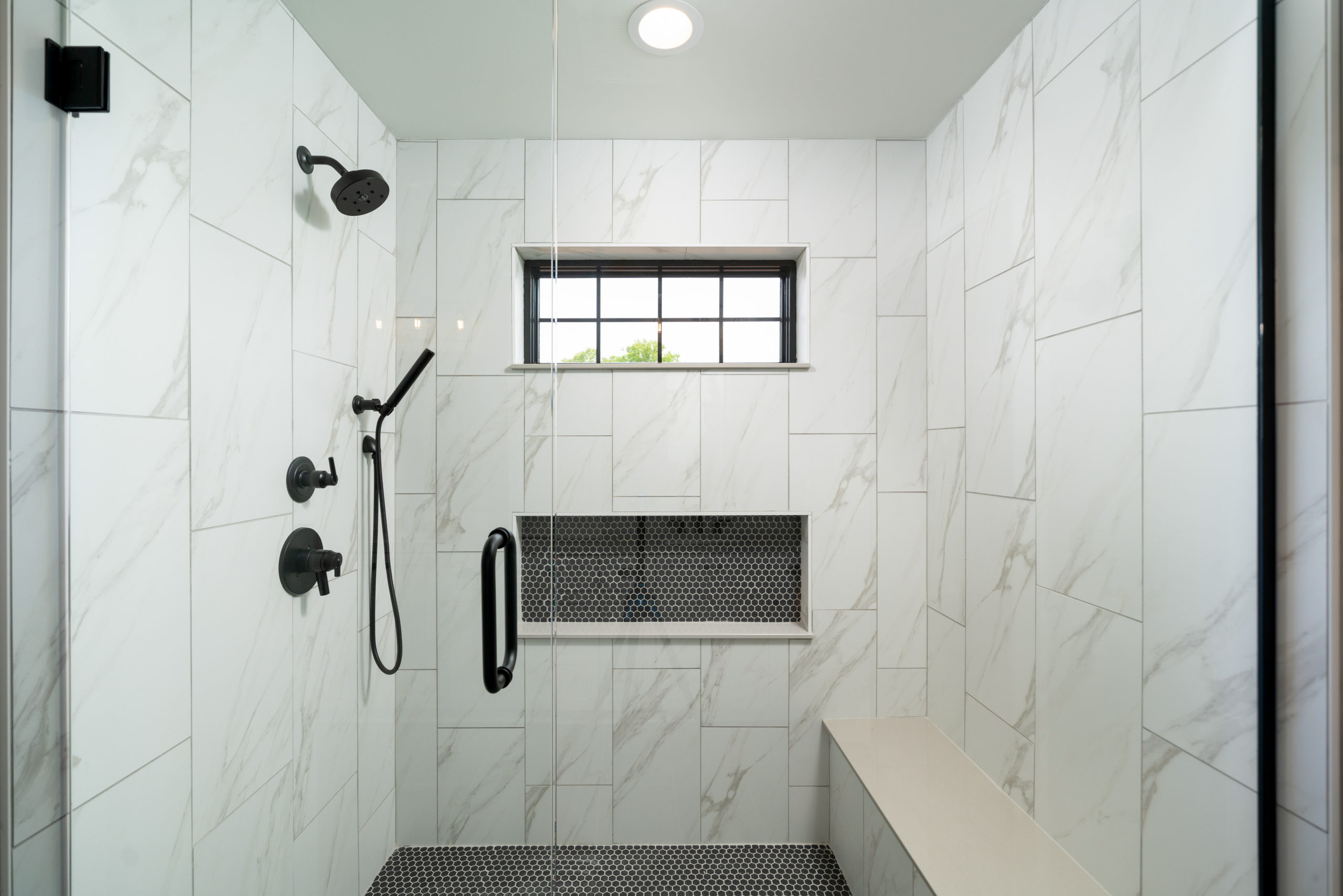 marble tiled shower with custom bench and shelf