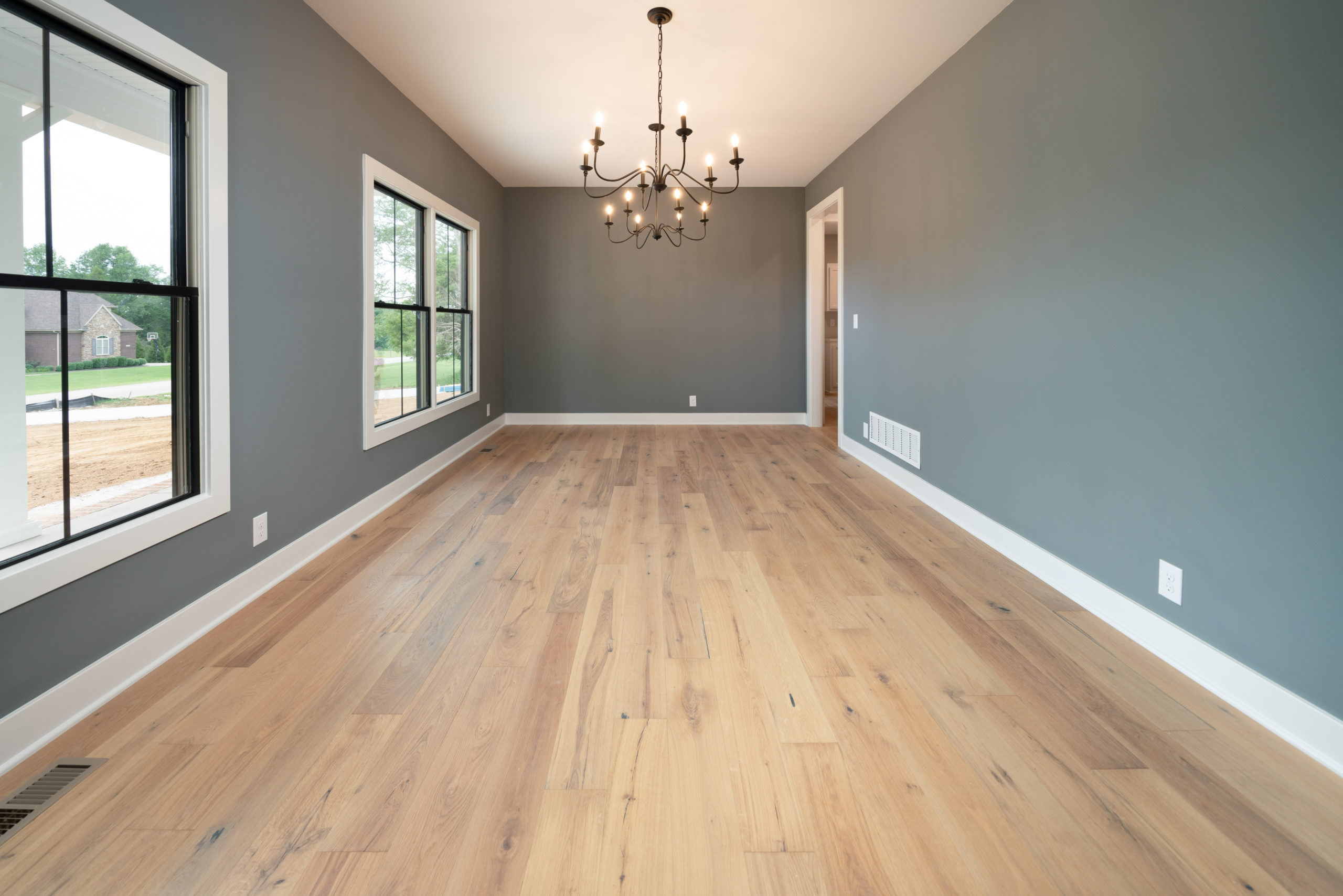 formal dining room with light hardwood floors and gray-blue walls