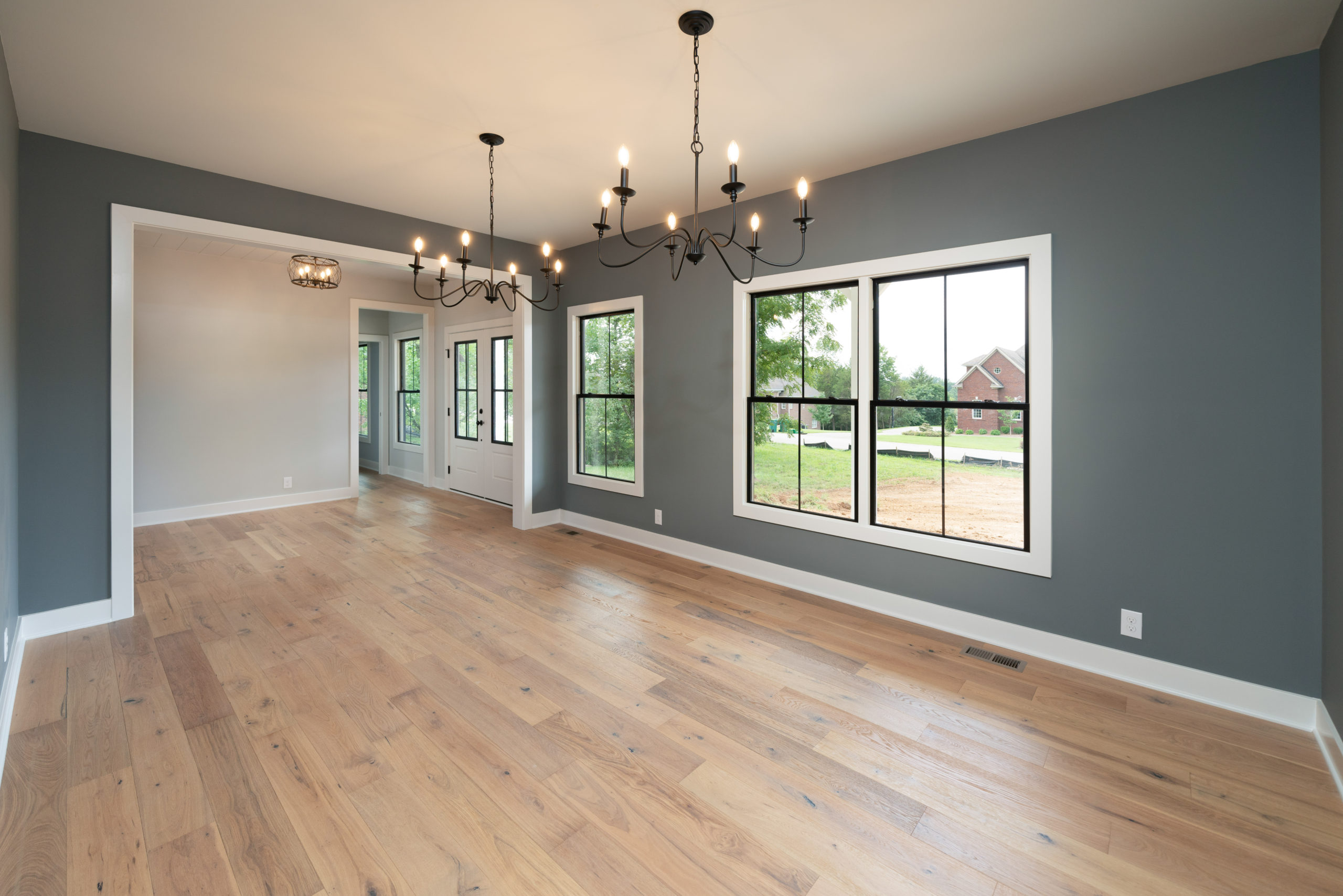 large formal dining room with two chandeliers