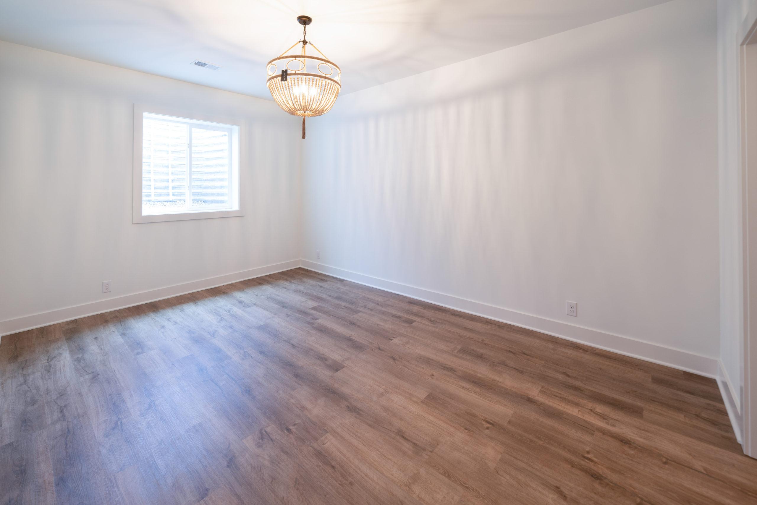 downstairs bedroom with hardwood flooring