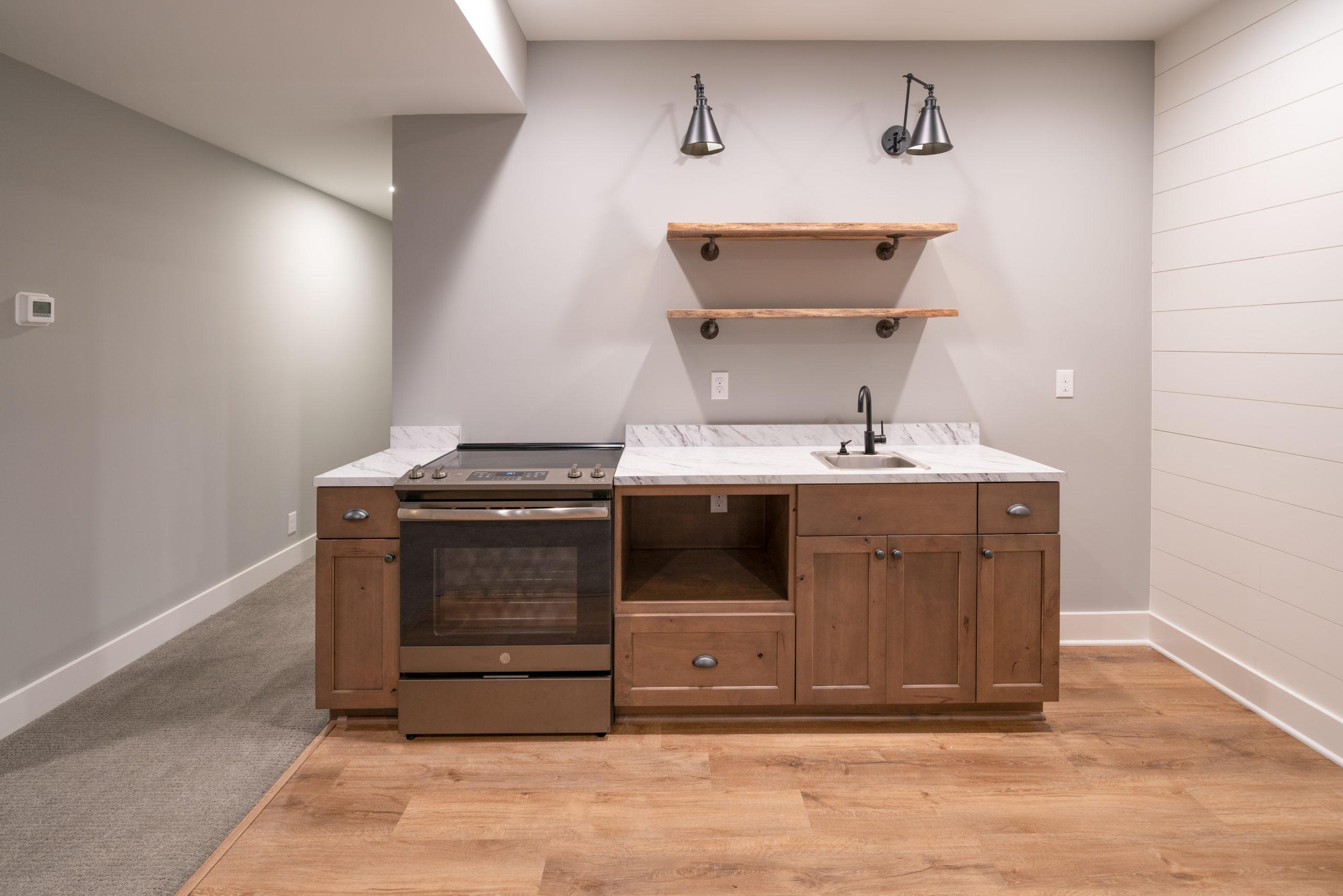 mini kitchen in basement with hardwood flooring