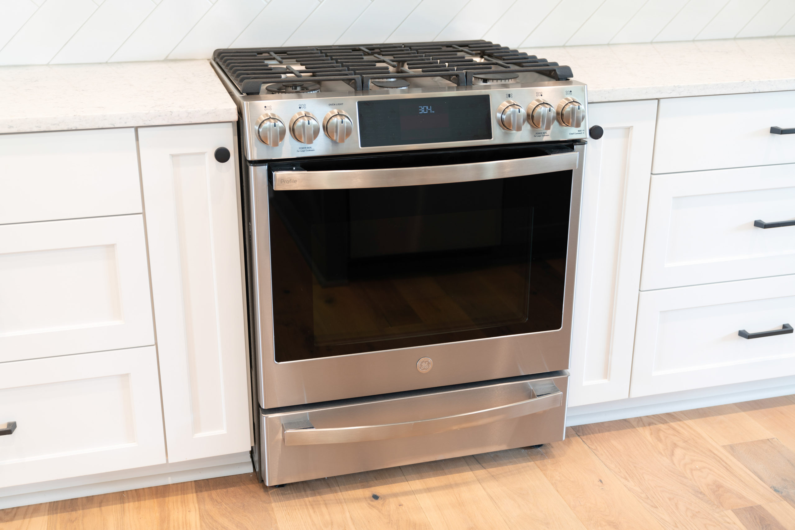 stainless steel gas stove in white kitchen with black hardware