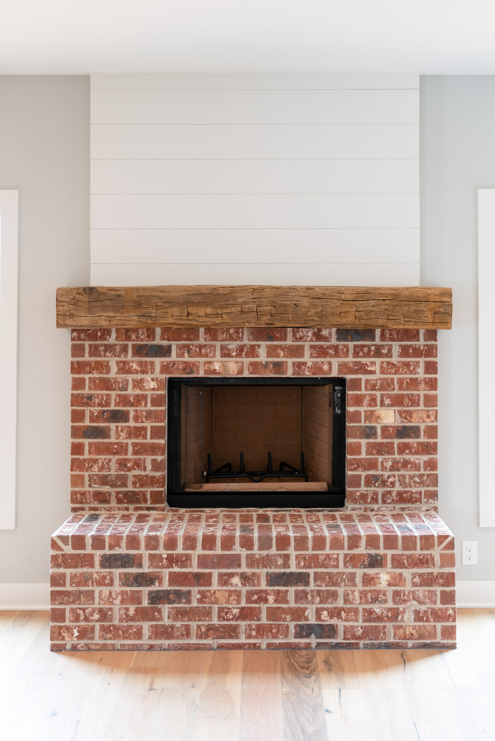 red brick fireplace with wood mantel and white shiplap