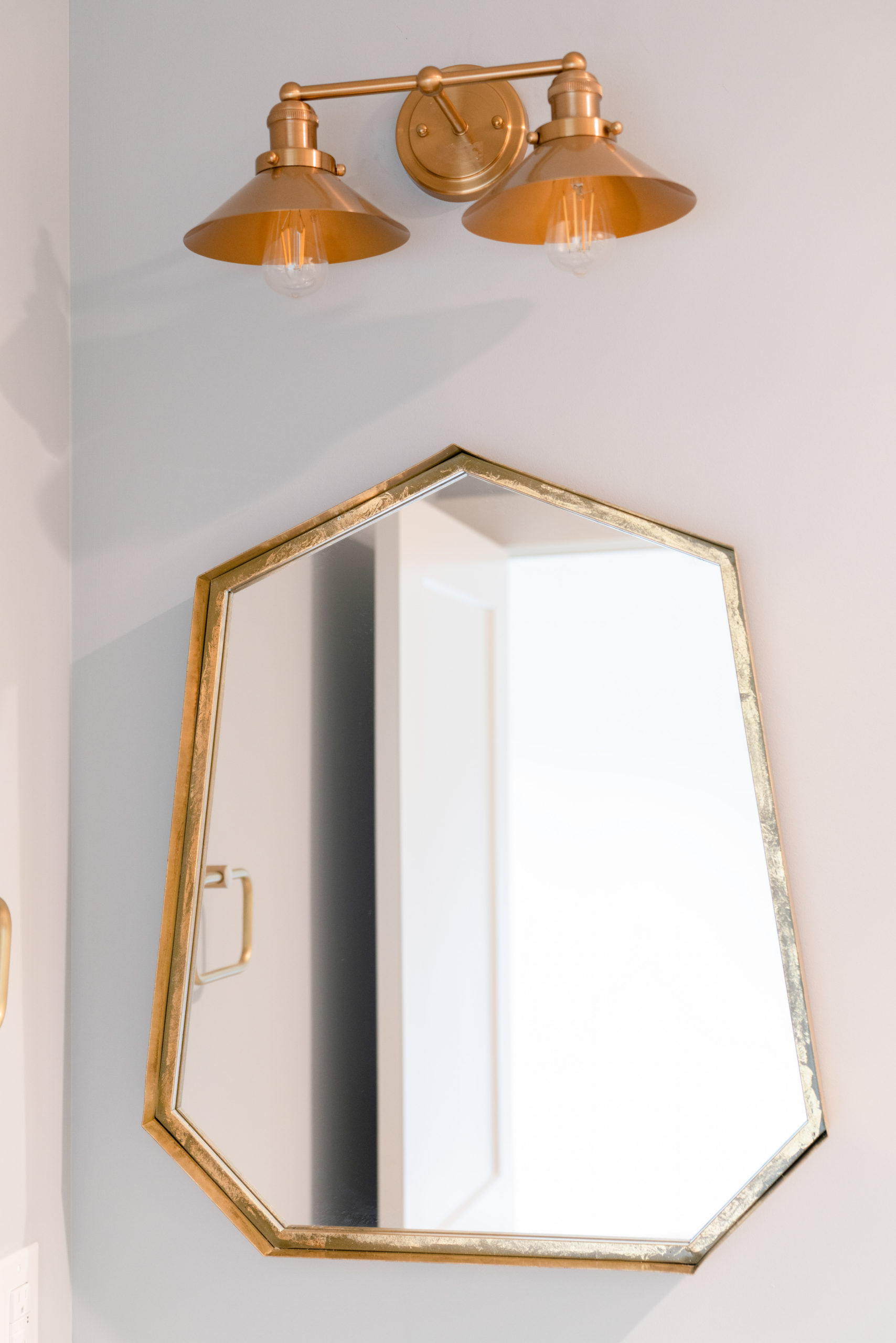 gold mirror in bathroom with gold light fixture
