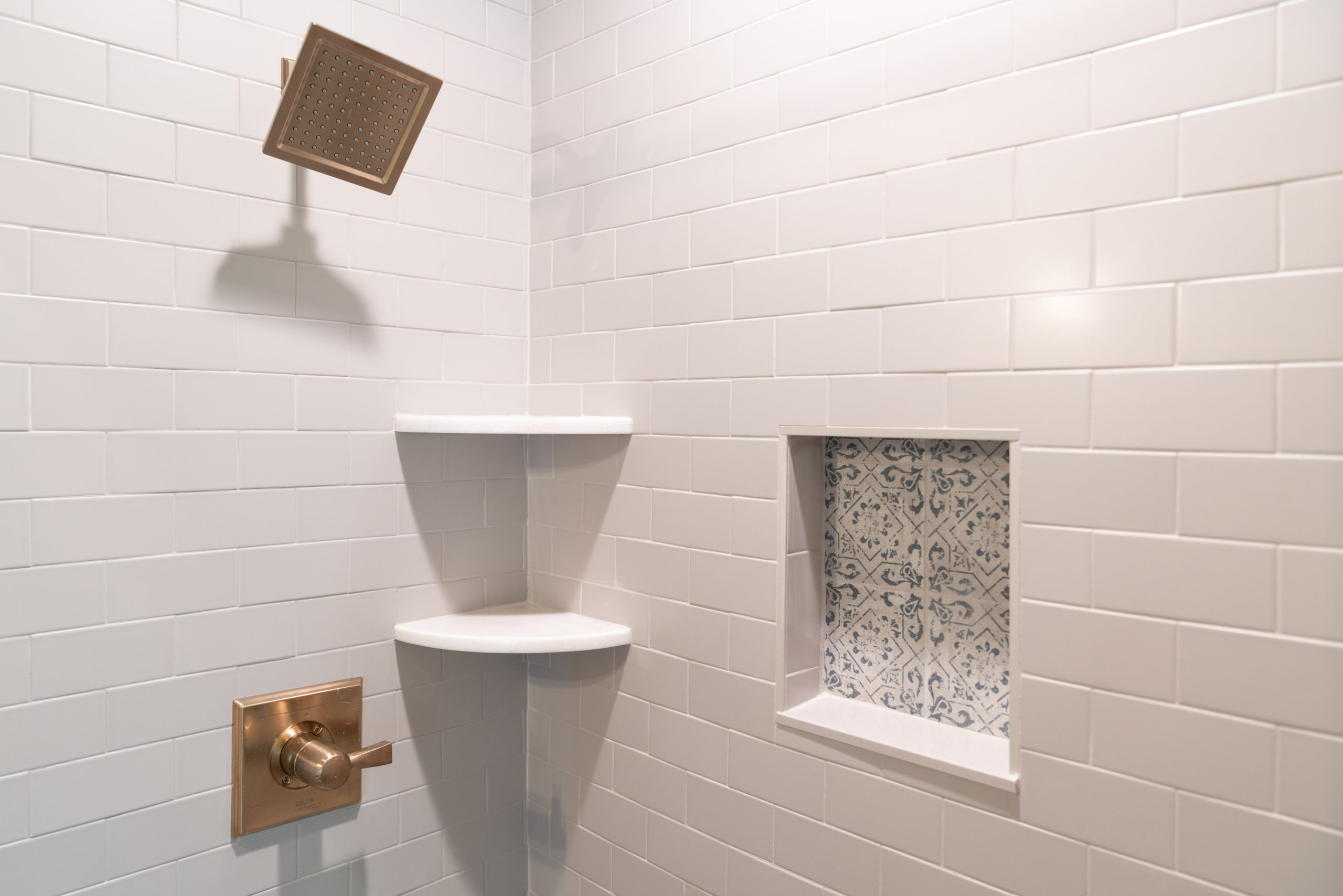 custom shower with white tile shelving and gold hardware