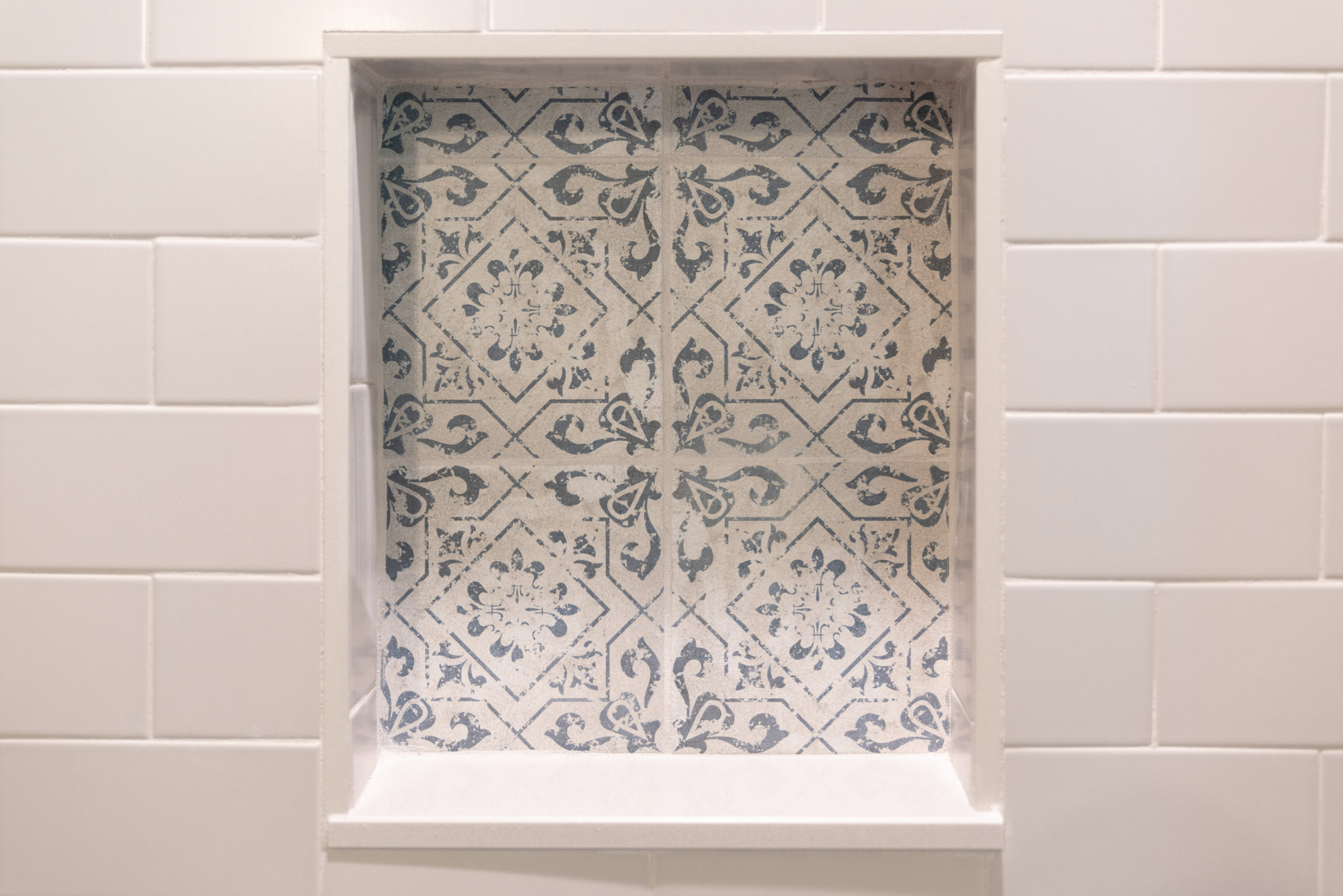 custom shower shelf with blue and white tile design