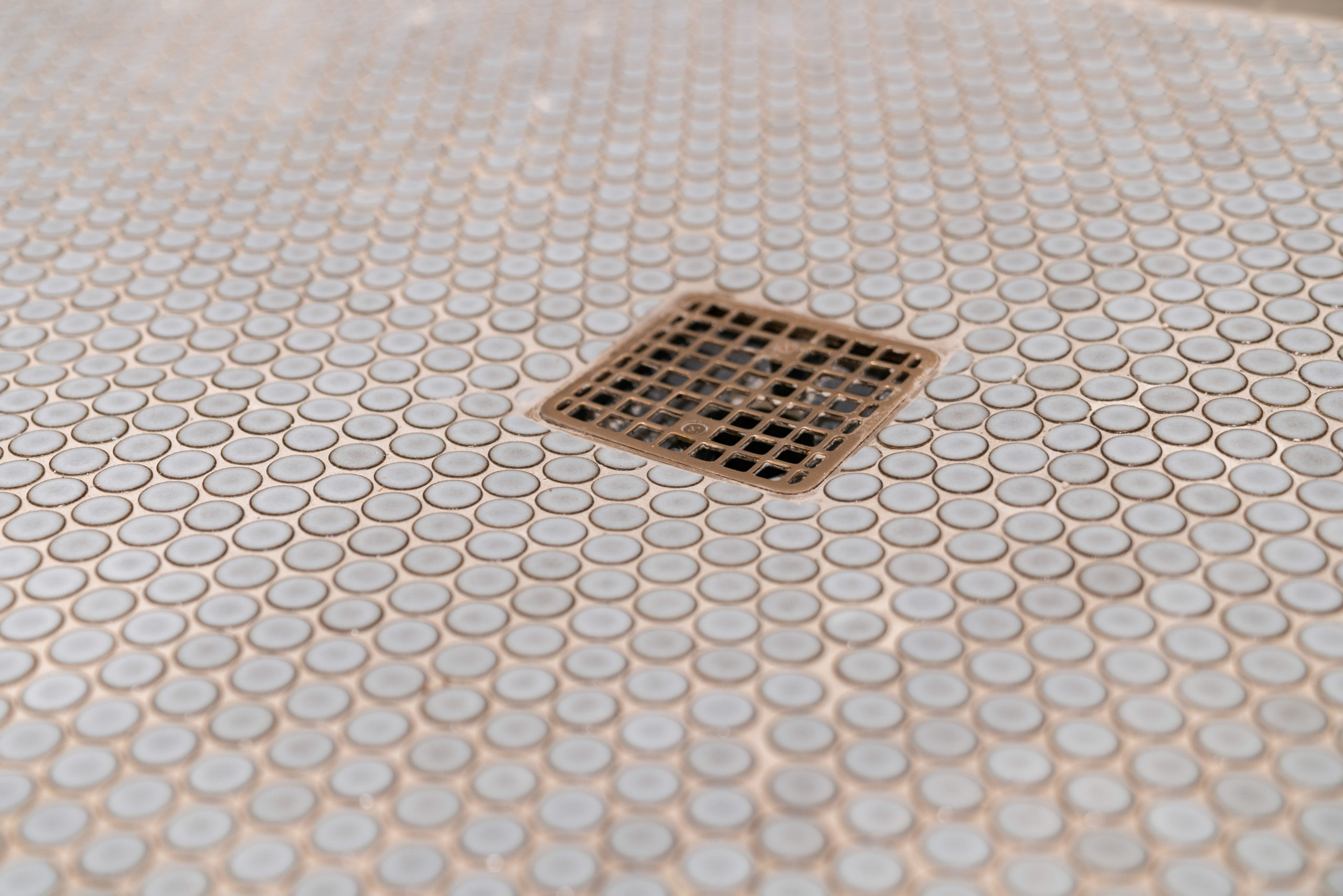 shower floor pebble tile with gold drain cover