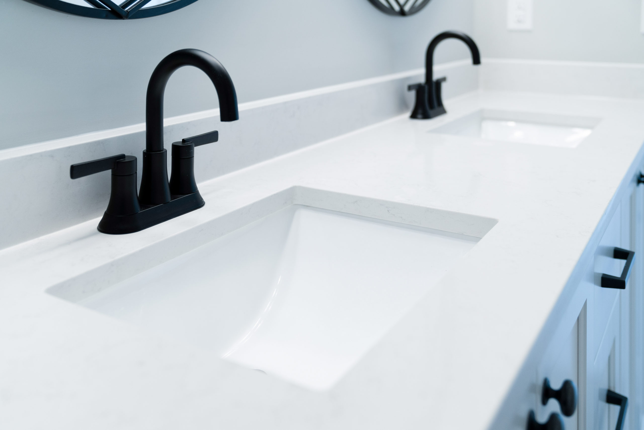 white bathroom countertops with black faucets