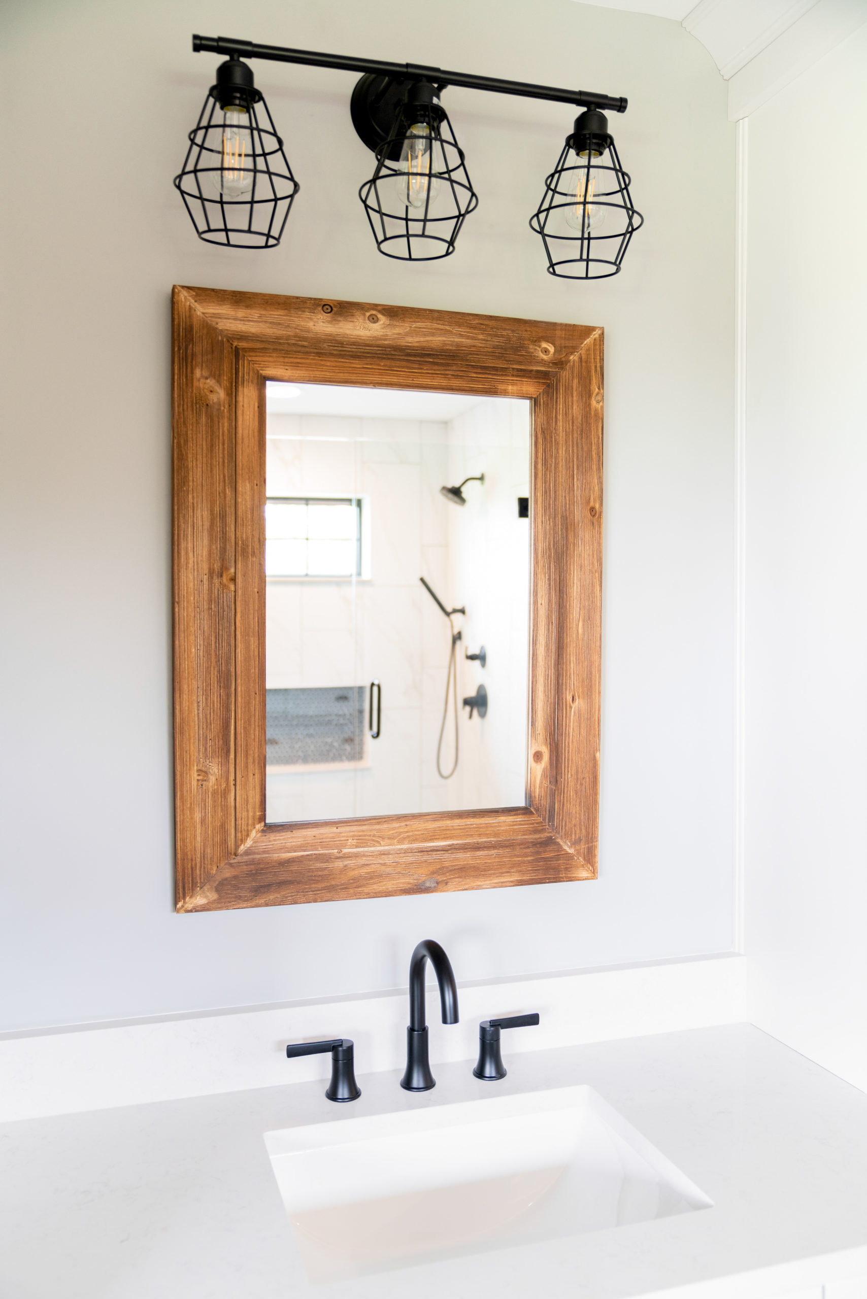 farmhouse bathroom with wood mirror and industrial light fixture