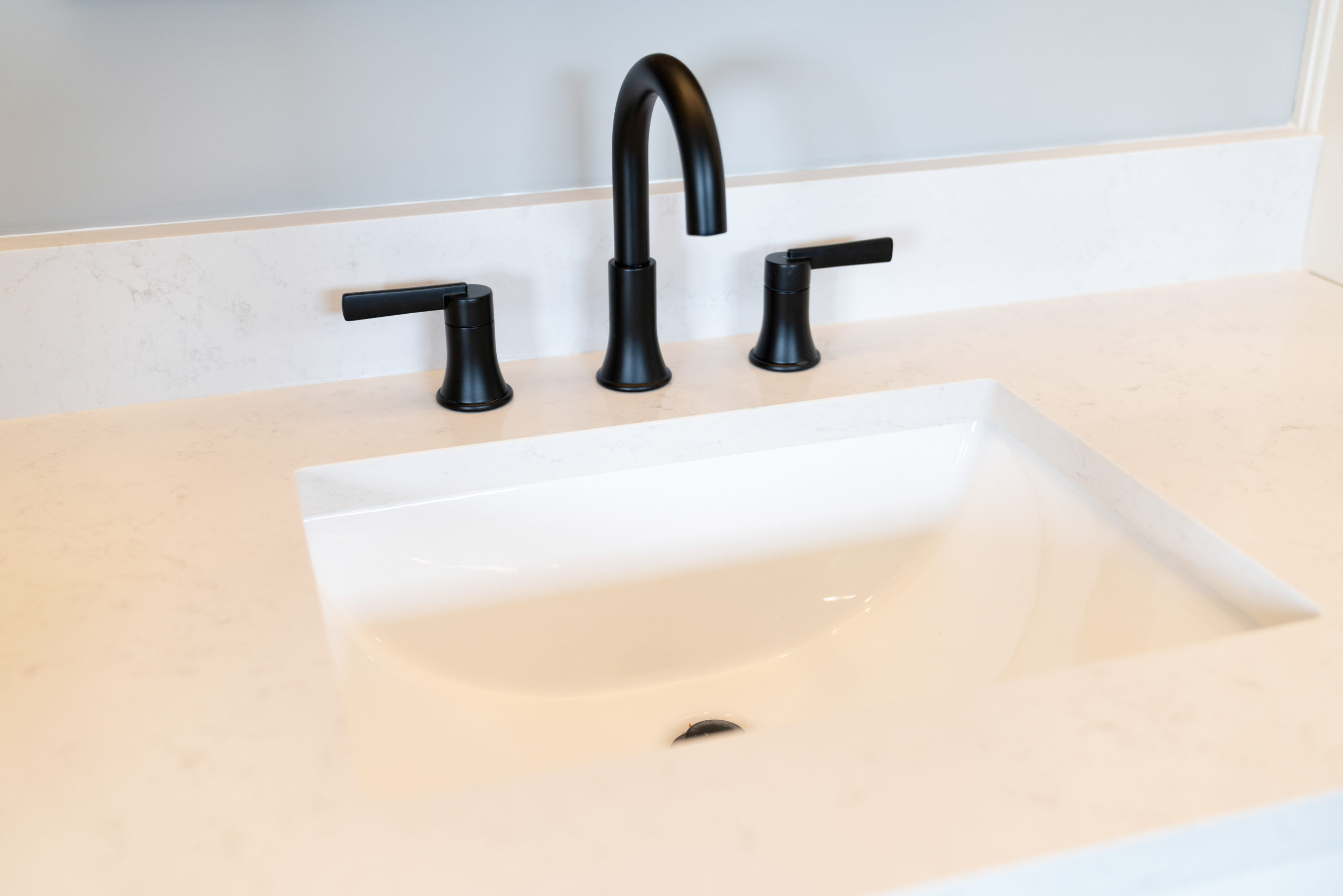 white bathroom counters with black faucet