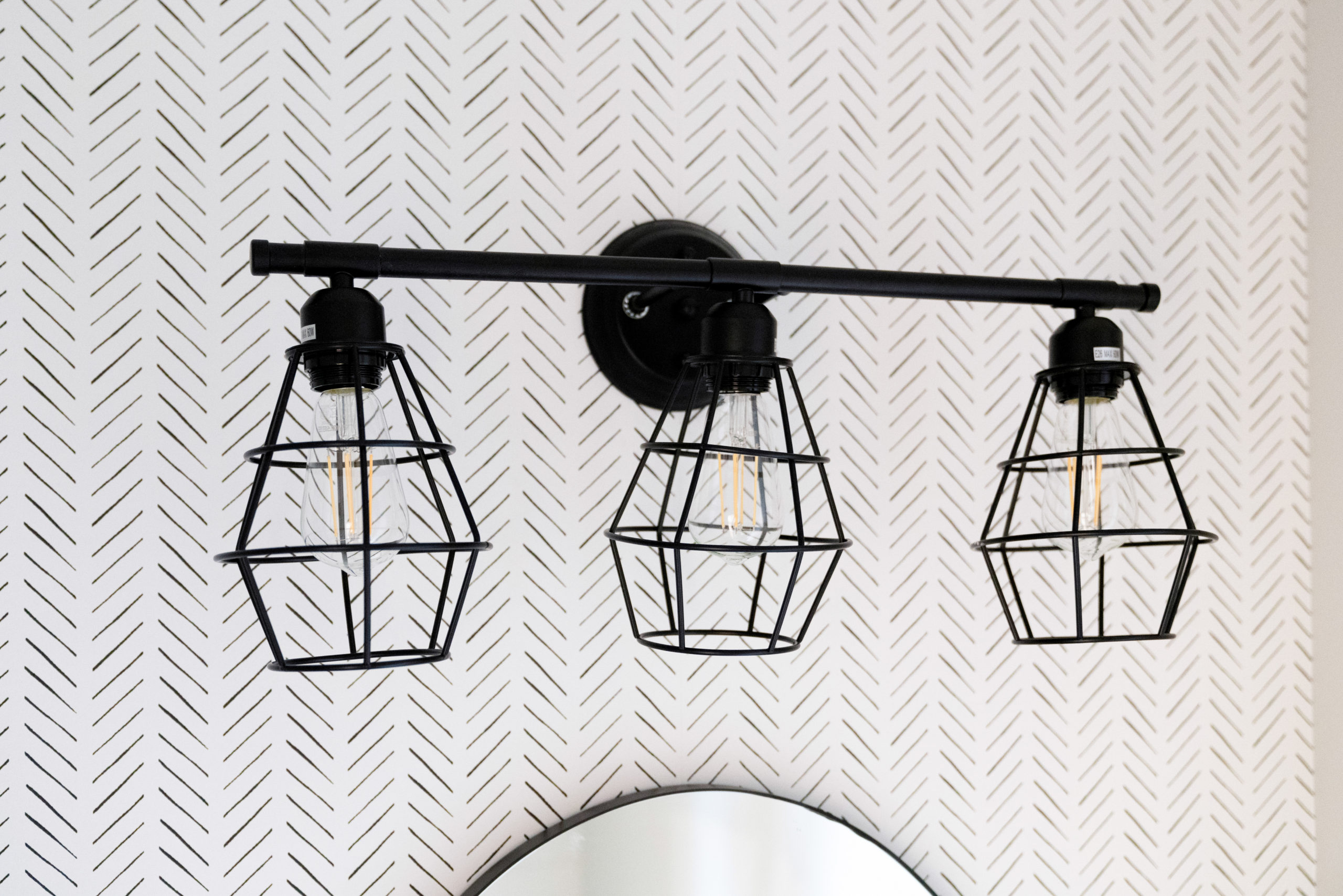 farmhouse powder room with wallpaper and industrial light fixture