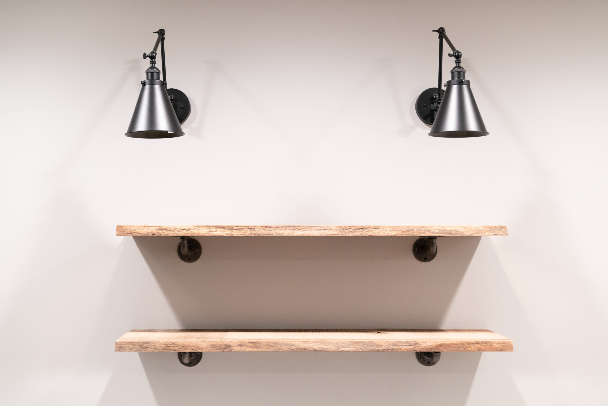 open mounted wood shelving with black sconces