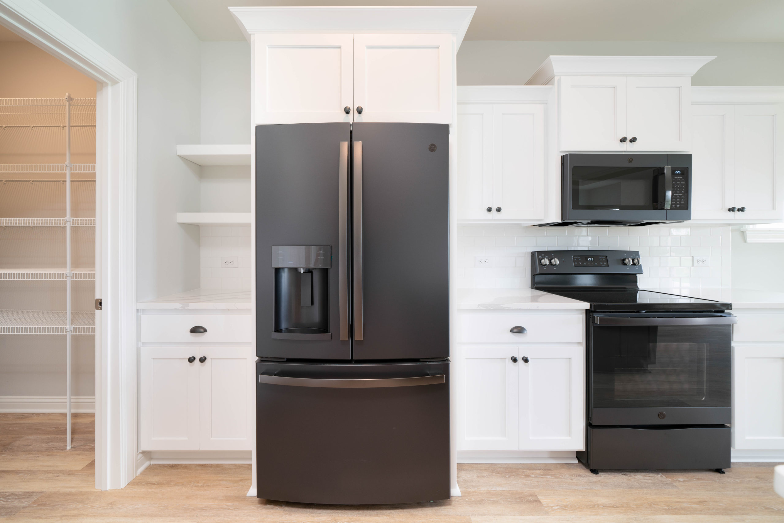 black kitchen appliances with white cabinetry