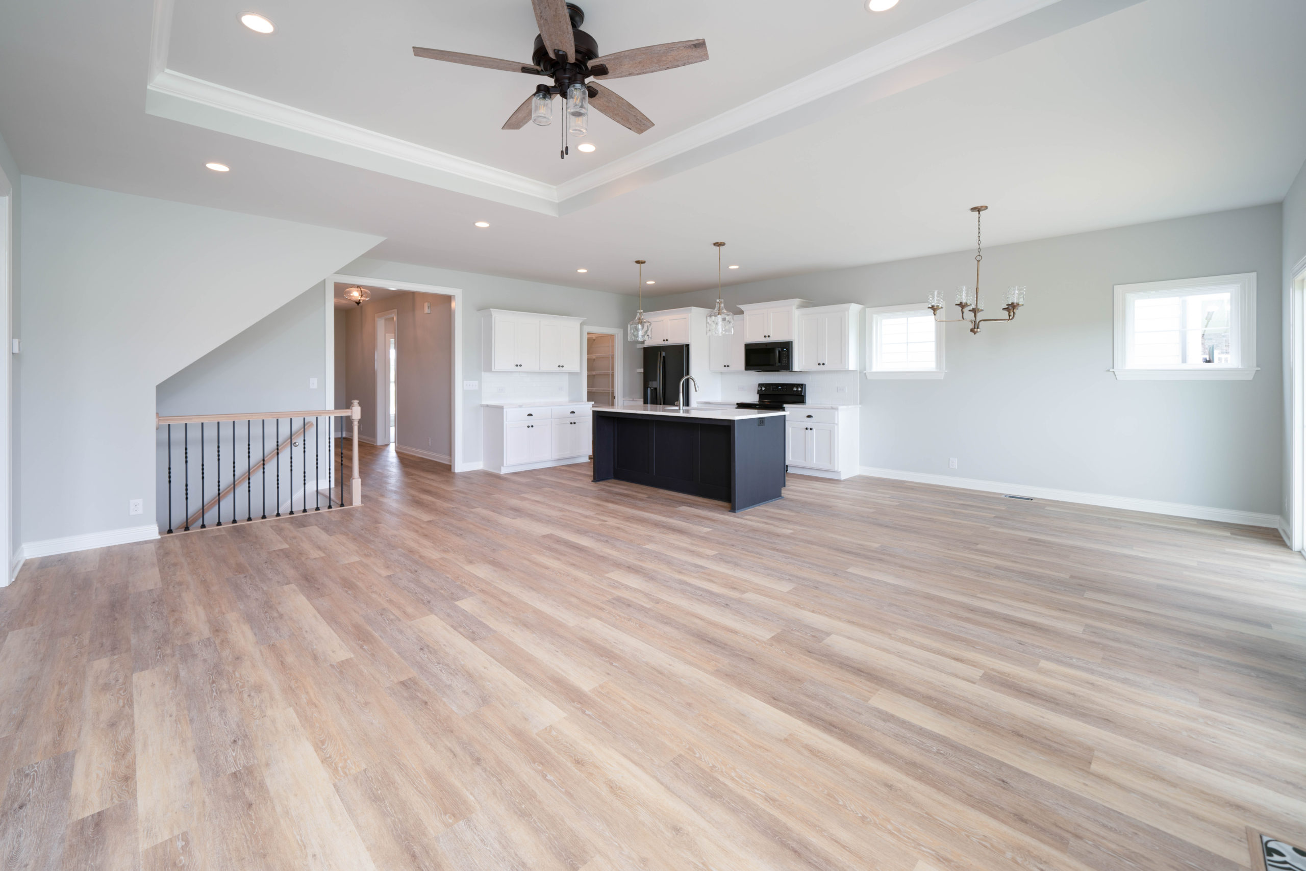 light hardwood floor living room with tray ceiling