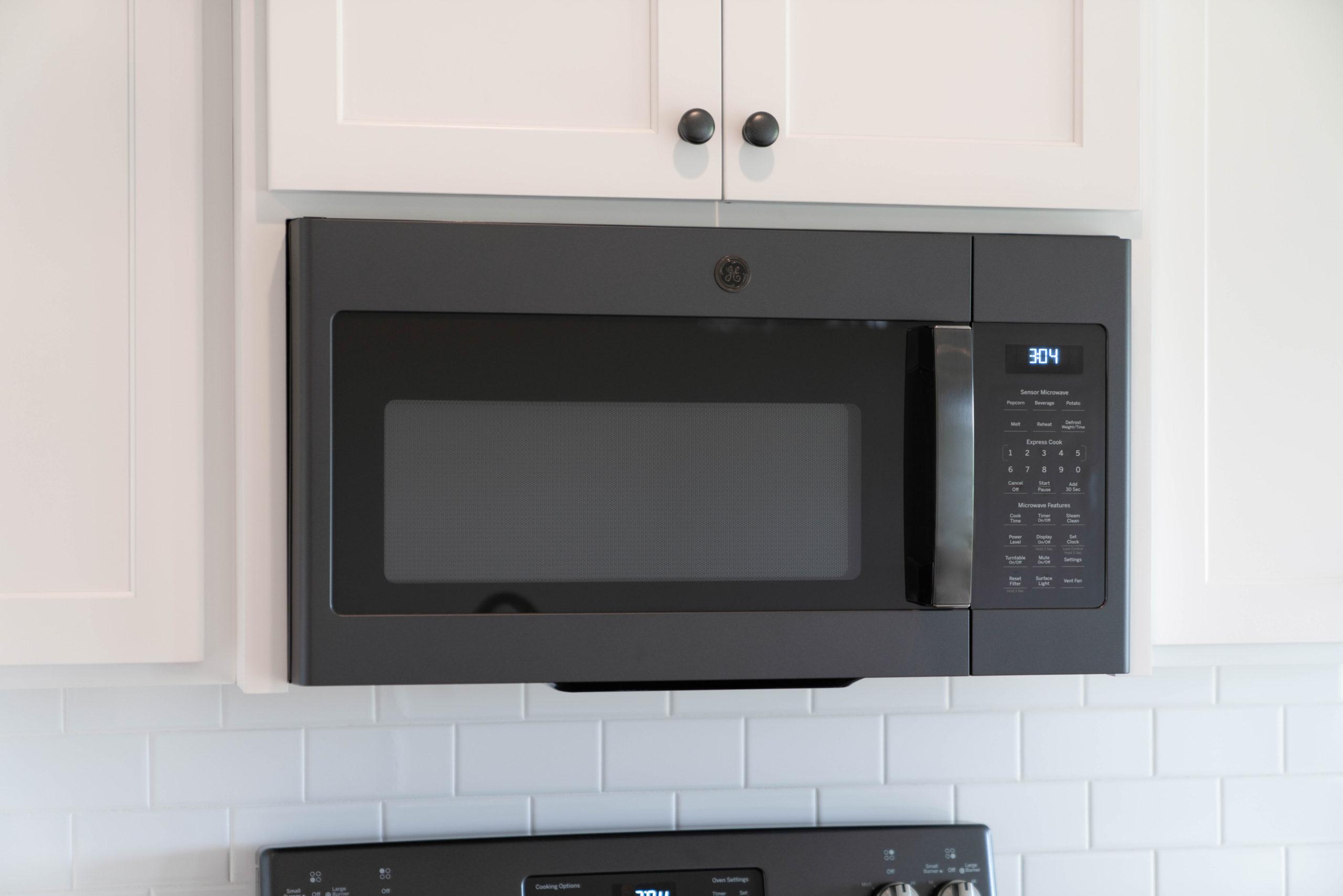 dark gray microwave in white kitchen