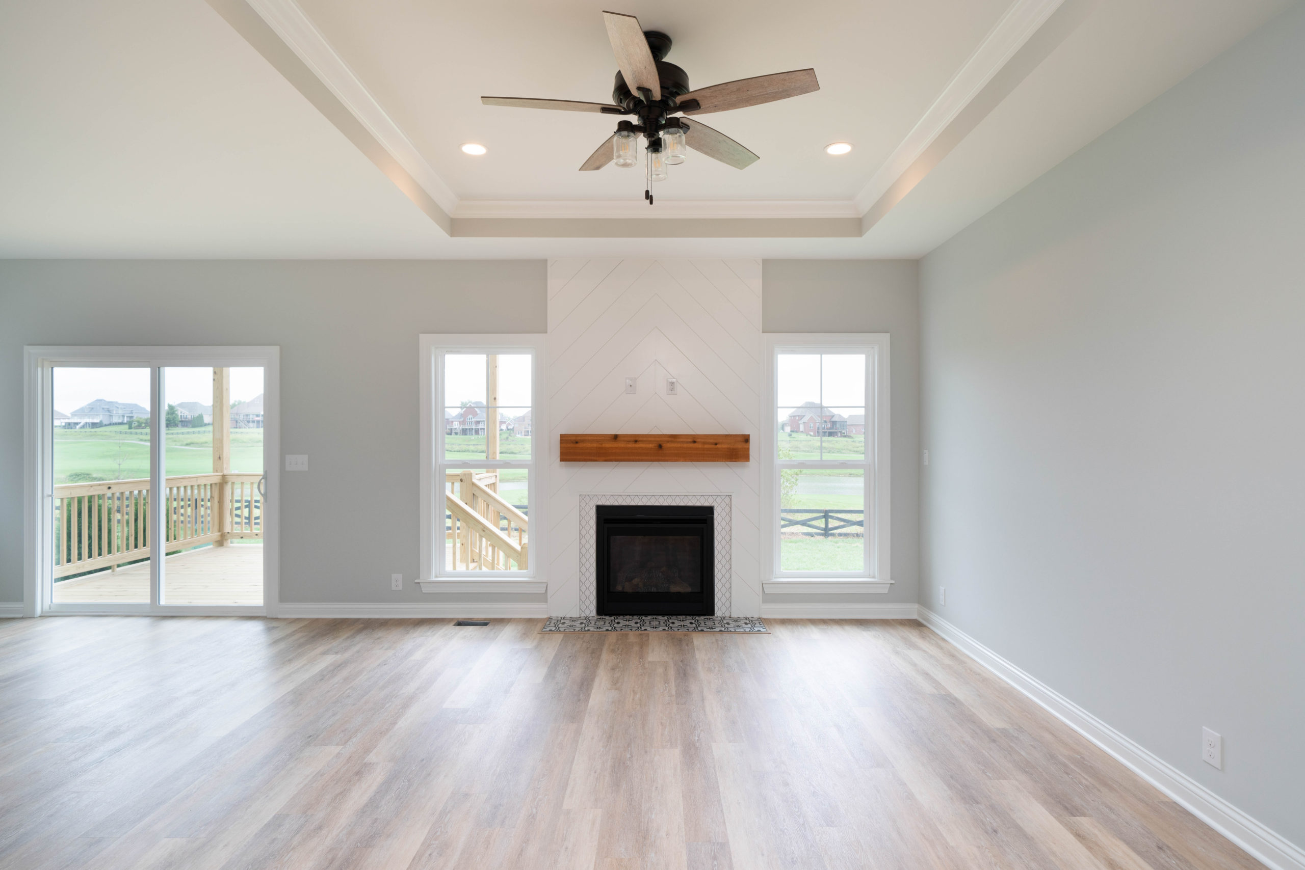 living room with tray ceiling and white shiplap fireplace with wood mantel