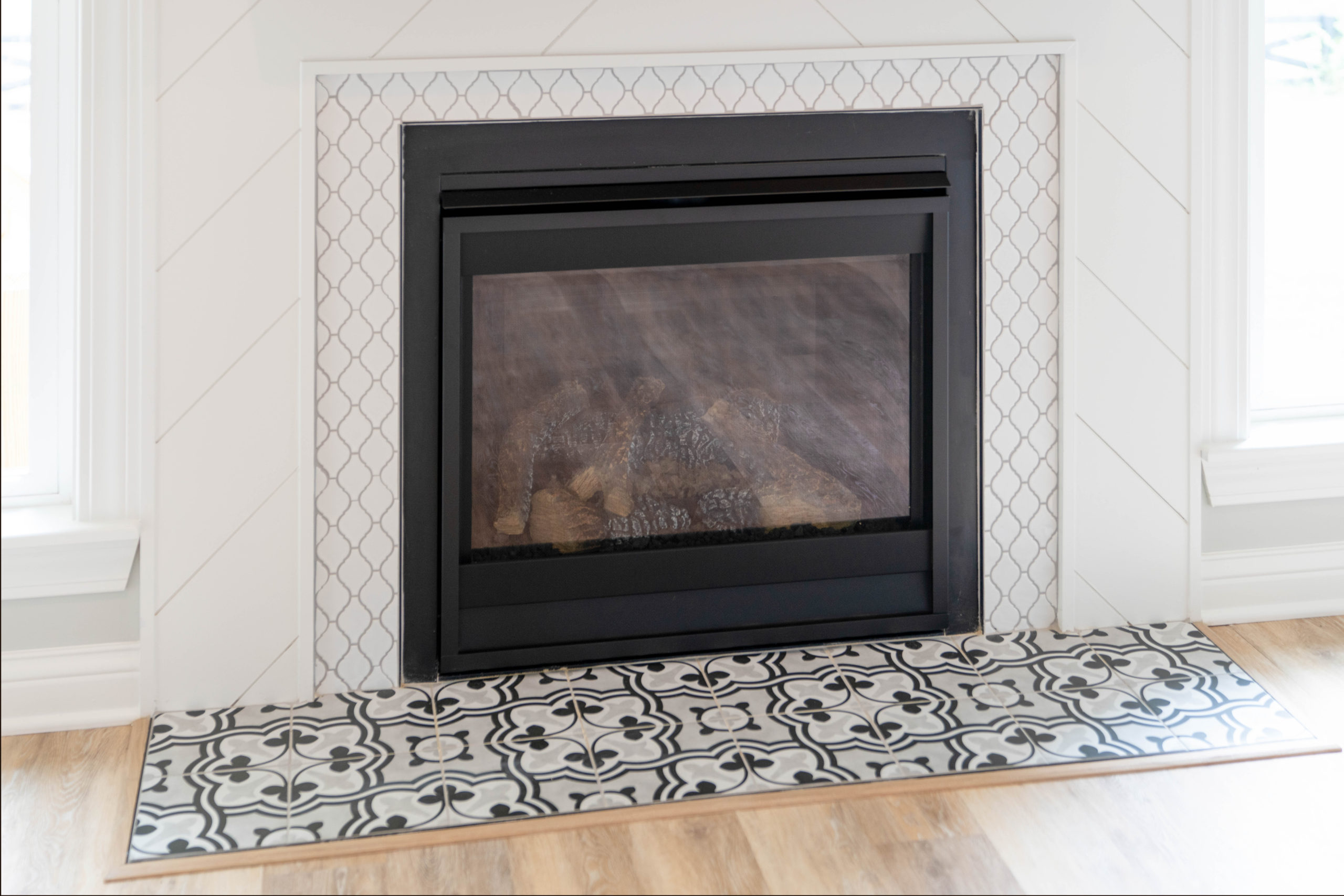 white tiled fireplace with geometric floor tile design