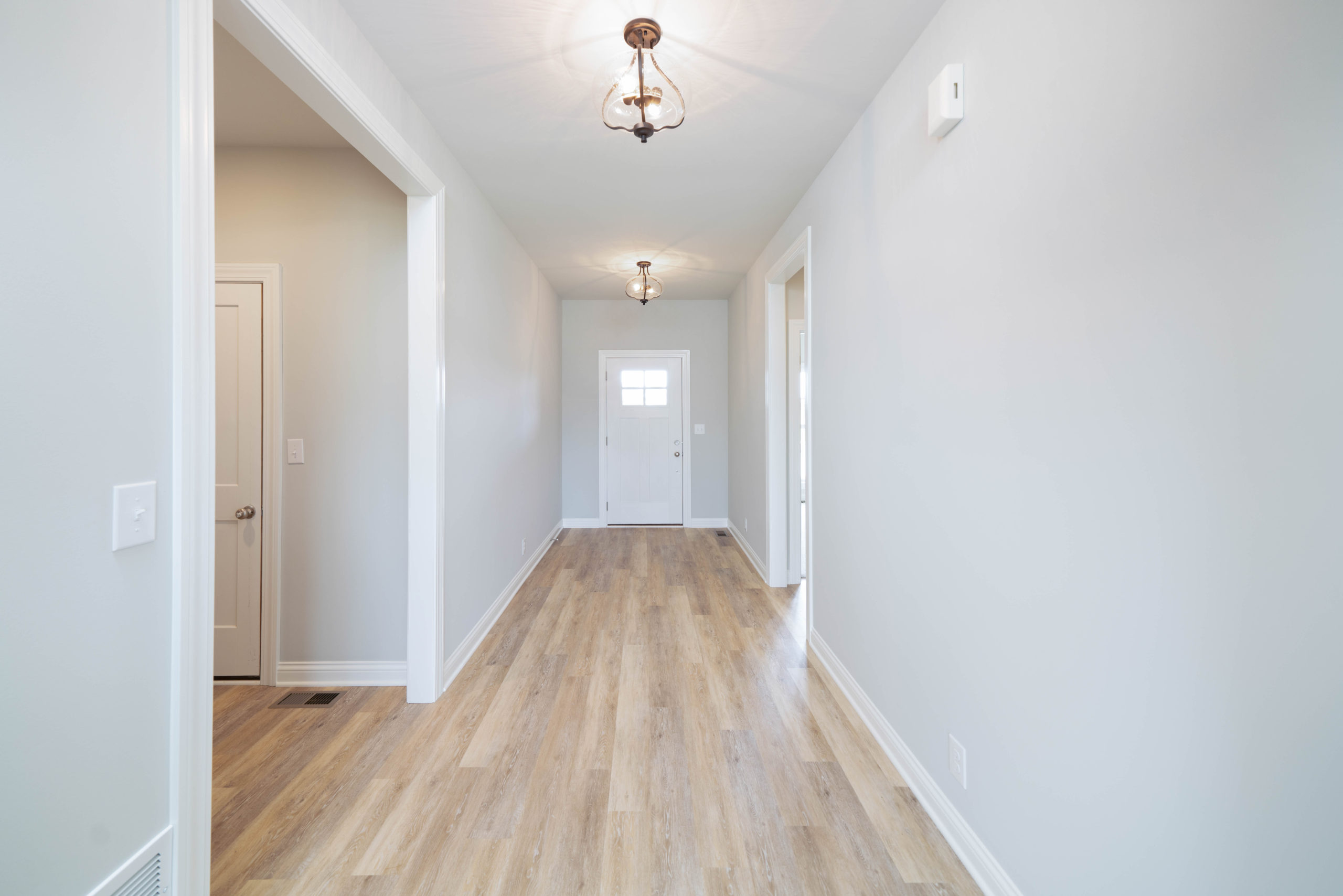 hallway with custom lighting and light hardwood floors