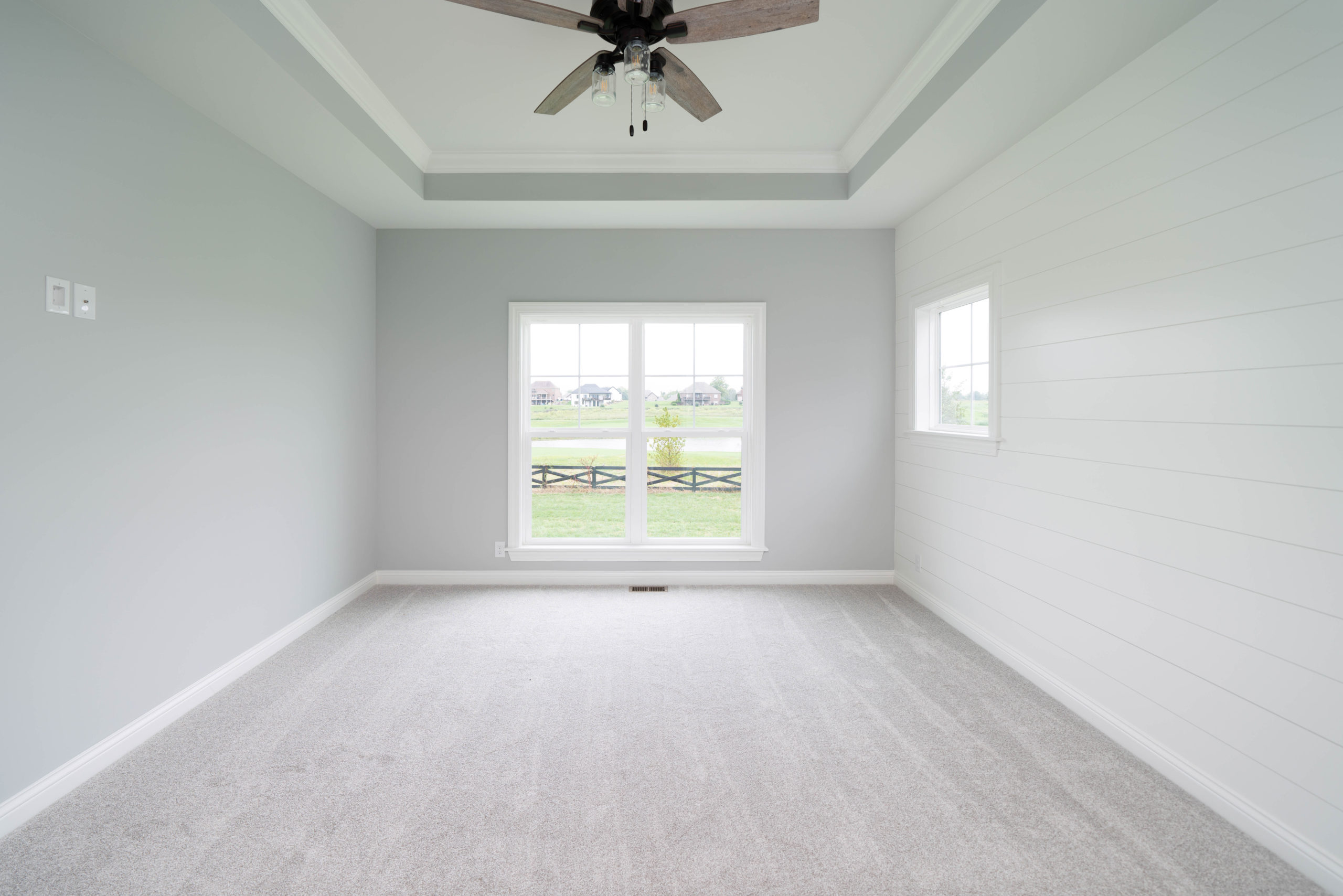 gray carpeted bedroom with tray ceiling