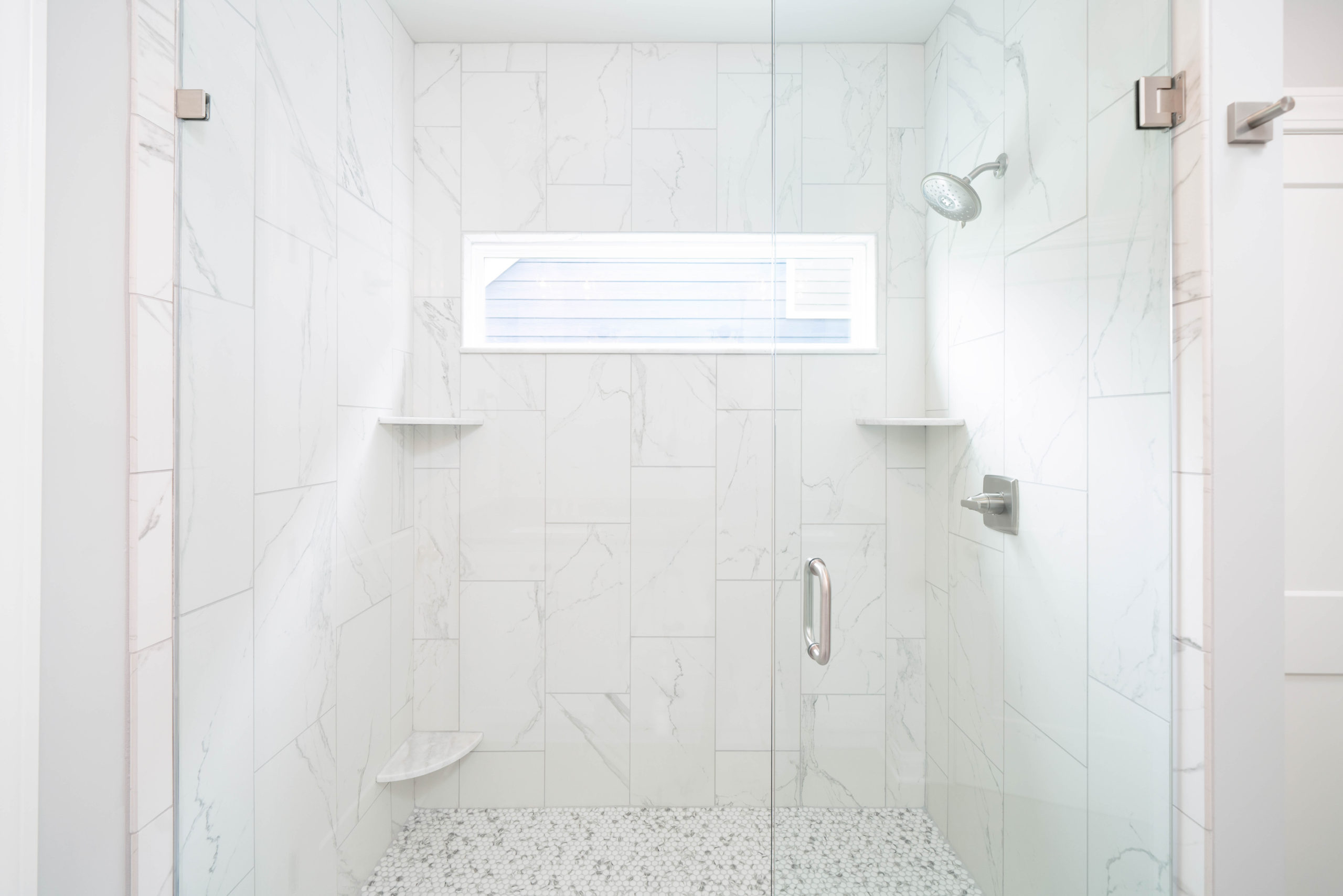 white marble tile shower with glass door