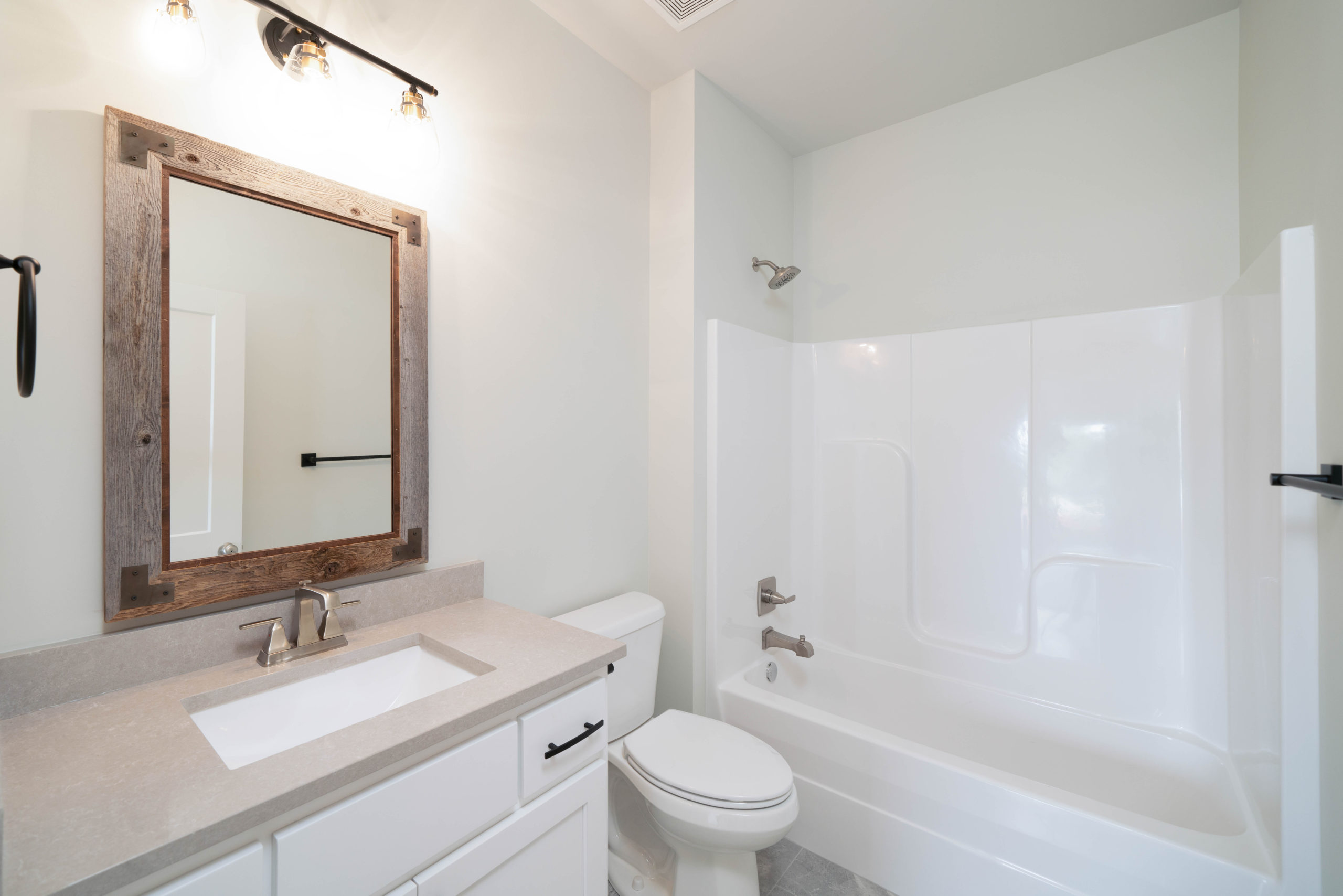 white bathroom with wood mirror