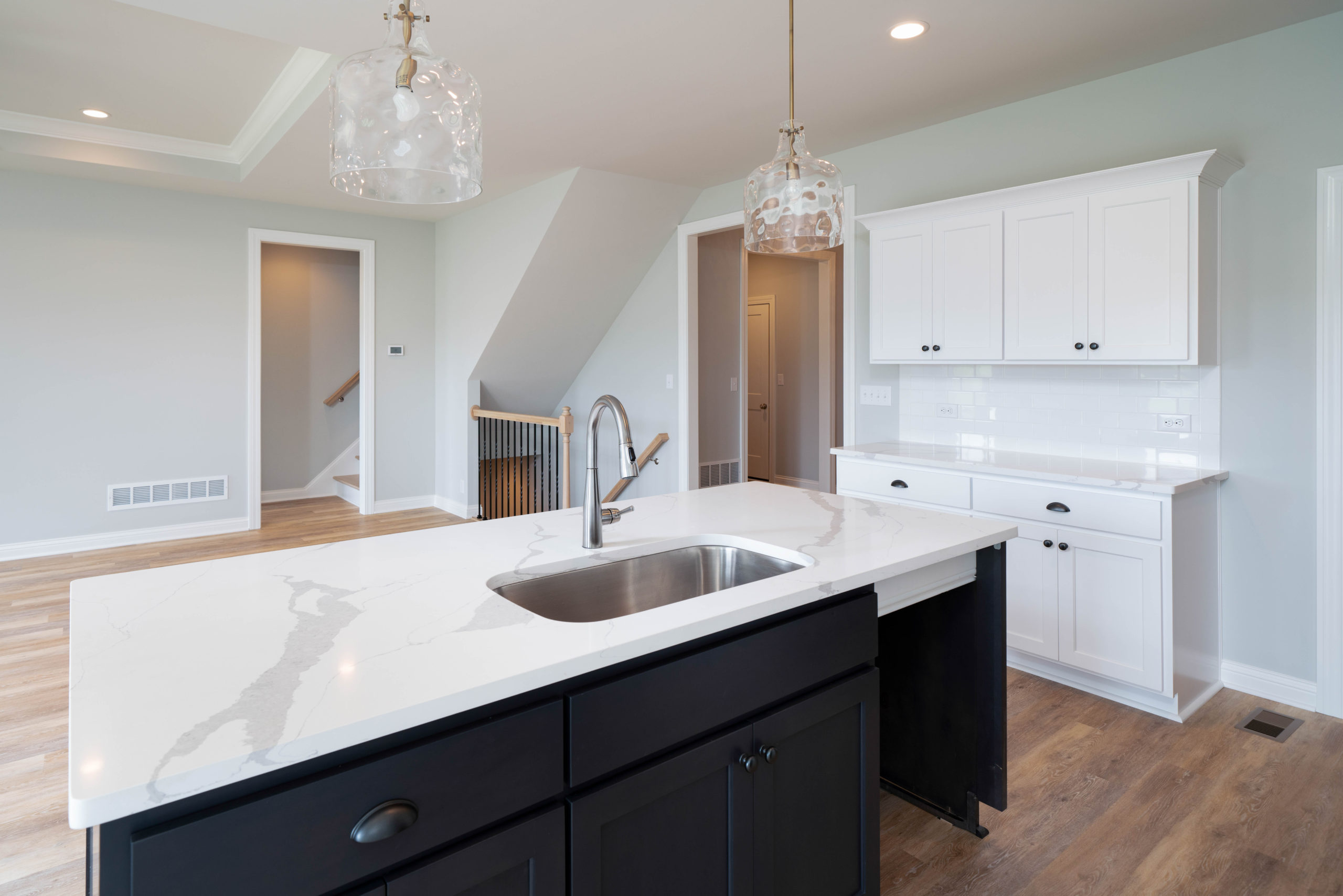 black kitchen island with white marble countertop
